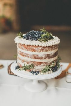 Yummy looking naked wedding cake topped with blueberries!
