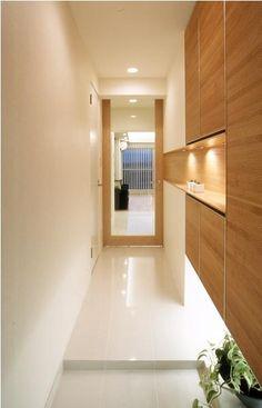 子どもスペースまで見渡せるオープンなキッチンで、家族の会話も華やぐ。リビングの大きな窓から差し込む光が玄関まで届き、明るい印象に。意匠性のあるリブ材の収納扉と、効果的に配された間接照明がモダンさを演出。