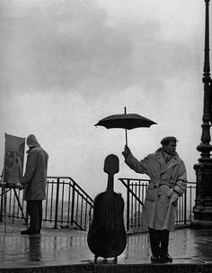 Dont't stop painting. Musician in the Rain, Robert Doisneau, 1957.
