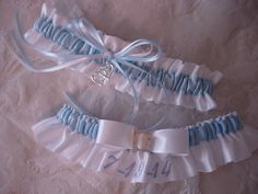 Keepsake and toss bridal garter set in traditional white and light blue. A sliver double-heart charm and rhinestone slide add sparkle.