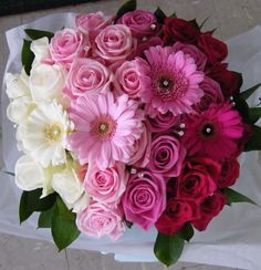 Shades of pinks from super pale to cerise pink, with roses & gerbera in a grouped bouquet