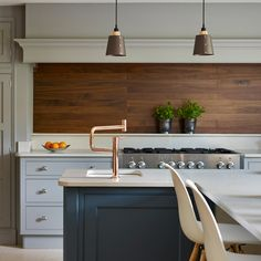 Texture and warmth is added to this stunning Martin Moore kitchen, martinmoore.com, with a sculptured walnut splash back. The metallic tap is a gorgeous addition that tones nicely with the timber feature.