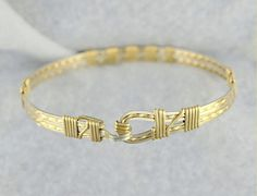 Fancy Steps is a contemporary version of the traditional wire wrapped bangle bracelet. The clasp is easy to operate with just a gentle squeeze of one hand. The bracelet is smooth to the touch on the inside and made with solid sterling silver and 14k gold filled wires.. This particular