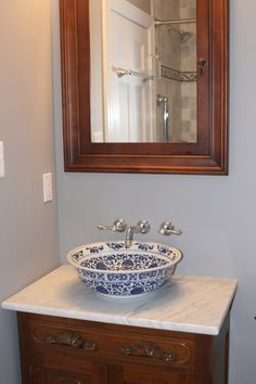 A china vessel sink we mounted on a marble-topped custom-modified antique vanity as part of an update to a 1920's colonial style home.