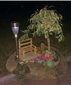 Mini jardín con banca y lampara solar plantado en una piedra