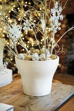 A Rafina Urn by Ballard Designs is filled with metallic ornaments and birch branches