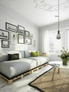 Sofa aus Paletten weißes Interieur zwei bunte Wurfkissen alle Blicke anziehen