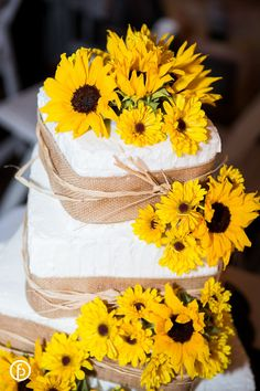 Rustic wedding cake with sunflowers, burlap, and twine accents.