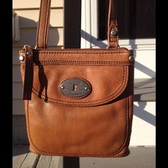 Fossil Crossbody Handbag Fossil Crossbody in very good Preowned condition.  This beautiful pebbled brown leather Crossbody handbag has one full front pocket with magnetic closure, with two credit card sized slots for organization.  Also the inside has one deep zippered pocket the width of the handbag.  The inside lining is Fossil signature lining. This adorable Crossbody has 1 mark on the back which you can see in the picture, but does not take away the beauty !  Original retail  $110…