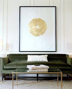 Groene sofa gecombineerd met goudkleurige salontafel met zwart blad en gouden schilderij.