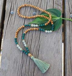 The Taurus Inspired Mala created using 8mm wood, Jade, Serpentine beads, and gold spacers and adornments, finished with a natural cotton tassel.