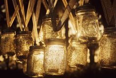 Hanging mason jars...would be really cute on the path down to the bonfire. We could even put citronella candles in them!