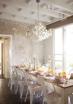 eclectic dining room design with white tolix chairs, rustic farmhouse dining table, crystal chandelier and metallic wallpaper.