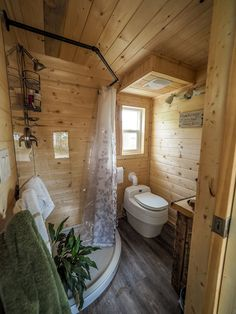 The bathroom includes a custom shower with acrylic clear walls and black pipe shower curtain rail, Separett composting toilet, and waterproof vinyl flooring.