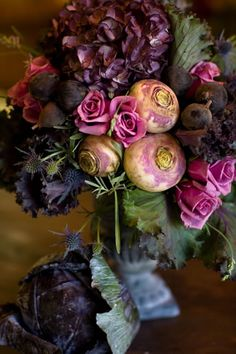 Floral arrangement stunner which includes vibrantly colored tea roses and produce from the garden patch in complimentary hues