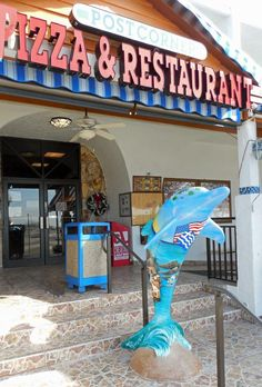 """The Greek"" dolphin is at Post corner Pizza, 431 South Gulfview Blvd., Clearwater Beach  Artist:  Adria Bernstein (Witty Wocks!)"