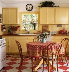 Lovely retro kitchen with yellow cupboards, white appliances, linoleum floor and a kitchen table