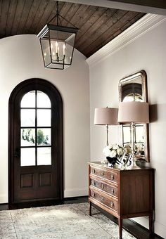 The entrance foyer with arched ceiling mirrors the shape of the door and incorporates a wood ceiling with a rustic lantern adding just the right amount of character. Simple, classic furnishings with just a touch of shimmer complement the rich wood hue.