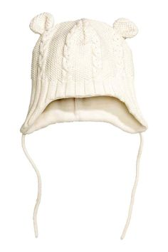 Fleece-lined hat: Cable-knit hat with decorative pompoms, earflaps and ties…