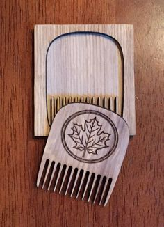 """This handmade comb is made of wood and sports our maple leaf logo. The comb measures 2"""" across and includes the wooden case. This is the perfect comb to slide into your pocket when you are on the go."""