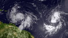 In this handout satellite image provided by NOAA, Isaac (left) reached tropical storm status and is approaching the Lesser Antilles islands as it moves westward on August 22, 2012 in the Atlantic Ocean.