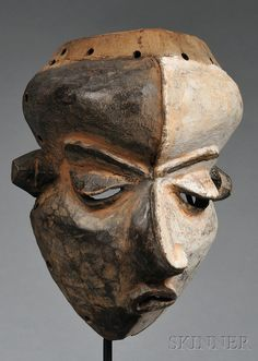 African Carved Wood Mask, Pende, Mbangu mask, with twisted face, pierced at mouth, eyes, and at edge for attachments, one side of face with white pigment, custom stand, ht. 8 1/2 in.  Sold for: $1,422