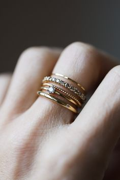 Building a perfect stack depends on finding rings that fit YOUR personality, and mixing textures and shapes to create something unique. From top to bottom we have the Golden Strand Stacker, Small Twinkle Band with Gray Diamonds, the Barely There Twist, the Six Prong Diamond Stacker, and the Petite Moonflower.