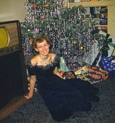 Vintage kodachrome. Lady in black cocktail dress in front of Christmas tree.