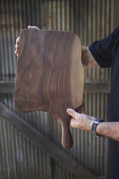 Black walnut wooden cutting board with handle and blonde streaks.