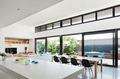 Open space plan, large island, contrast of black framed sliders against white. Very graphic.