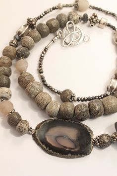 "Jill Duzan — Stella - Designed with prehistoric Stegodon bones, Stella is one-of-a-kind and spectacular! With interesting shades of gray, a horn in black, Thai silver and a distinctive Agate, the details pull it all together. 40"" of Stunning!"