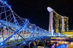 Glamour shot of Helix Bridge and Marina Bay Sands Casion Hotel at night, the…