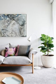 Mod living space with a gray and wood sofa, a white floor lamp, and a fiddle leaf fig