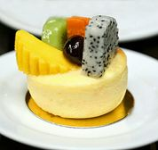 Mango Cheesecake (gluten-free): Mango Cheesecake, served here with slices of mango, dragonfruit, papaya, kiwi, and a cherry (this cheesecake can also be served with a mango topping - see recipe)