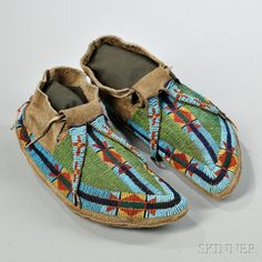 Lakota Beaded Buffalo Hide Moccasins, c. 1870s, with beaded bifurcated tongues and multicolored geometric designs, remnant tin cone and horse hair danglers, lg. 10 1/2 in. Estimate $3,500-4,500