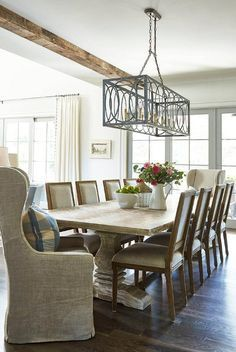 Rustic cottage dining room boast a whitewashed trestle dining table seating two gray linen wingback captain's chairs and eight light gray French square back dining chairs lit by a gray iron rectangular chandelier hung from a ceiling accented with rustic wood beams.