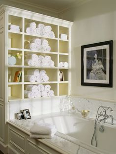 marble bath tub, silver hardware, shelf unit on the side loaded with towels and books and toiletries