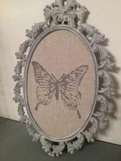 Cadre métal oval patiné gris fond lin papillon encré
