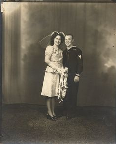 Early 1940s, during the war. Thus the short skirt and simple suit, and navy uniform.