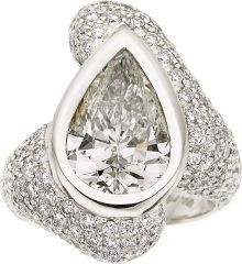 Diamond, White Gold Ring  The ring features a pear-shaped diamond measuring 15.40 x 10.50 x 6.10 mm and weighing approximately 6.90 carats, enhanced by pavé-set full-cut diamonds weighing a total of approximately 3.50 carats, set in 18k white gold. Total diamond weight is approximately 10.40 carats.