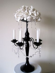 Black and White Wedding Reception Centerpiece Black Candelabra With White Roses. Keywords: #weddingreceptioncenterpiece #jevelweddingplanning Follow Us: www.jevelweddingplanning.com  www.facebook.com/jevelweddingplanning/