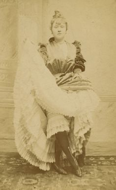 La Goulue (Louise Weber) posed dancing  Albumen print, Cabinet card, mid 1870s to late 1870s  With the photographer's name, location and the Moulin Rouge red mill printed mount recto. NOTE: La Goulue was the French cancan dancer depicted in many of Toulouse-Lautrec's paintings