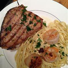 Grilled Marinated Swordfish Recipe :         4 cloves garlic        1/3 cup white wine        1/4 cup lemon juice        2 tablespoons soy sauce        2 tablespoons olive oil        1 tablespoon poultry seasoning        1/4 teaspoon salt        1/8 teaspoon pepper        4 swordfish steaks