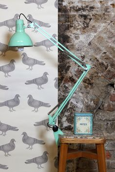 Vintage Anglepoise lamp and vintage tin contrasting with modern wallpaper