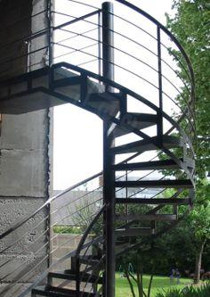 Photo DH33 - SPIR'DÉCO® Mixte. Escalier hélicoïdal contemporain avec départ balancé et évasé pour l'extérieur en métal et béton. Marches pour béton. Limons en tôle roulée découpés façon charpente métallique y compris rivets en fer forgé décoratifs pour un design de style industriel. Finition : acier brut à vernir pour l'extérieur. - Modèle déposé - © Photo : Escaliers Décors®