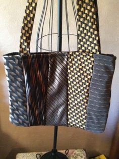 I made this bag out of ten coordinating neckties in blacks, browns and golds. It is lined with a black polyester fabric and has a velcro closure. It measures approximately 14 inches wide and 11 inches deep. The shoulder strap measures 37 inches.  FREE SHIPPING