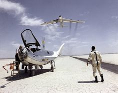 NASA research pilot Bill Dana takes a moment to watch NASA's NB-52B cruise overhead after a research flight in the HL-10. On the left, John Reeves can be seen at the cockpit of the lifting body. The HL-10 was one of five lifting body designs flown at NASA's Dryden Flight Research Center, Edwards, California, from July 1966 to November 1975.
