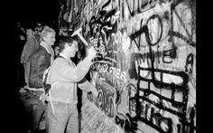 Homem martela parte do Muro de Berlim, próximo ao Portão de Brandemburgo, após a abertura da fronteira da Alemanha Oriental ser anunciada em Berlim. Foto de 9 de novembro de 1989