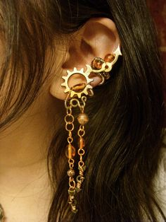 "Made with copper, aluminum, pewter, and amber beading, this warm re-imagining of my original slave ear cuff creation is inspired by the romantic Victorian industrial style known as Steampunk or ""What could have been""    These two ear cuffs embody the heart and mind of The Trinket Collector. This unfortunate soul who has no possessions outside of the ones they find while fulfilling their duty to the ones who own them. Dark and twisted but with a hint of fighting fire, they are the most potent ..."