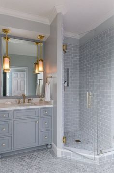 bathroom combines grey subway tile on the shower walls and grey marble hex tiles on the floors.